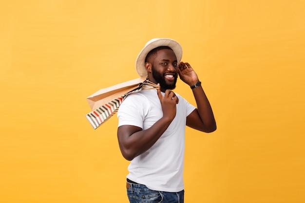 黄色の背景に分離されたカラフルな紙袋を持つアフリカ系アメリカ人の男