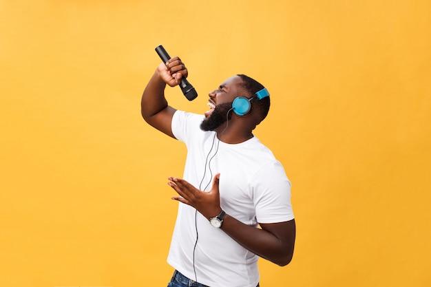 陽気な肯定的なシックなハンサムなアフリカ人男性のマイクを押しながらヘッドフォンを持っていることの肖像画