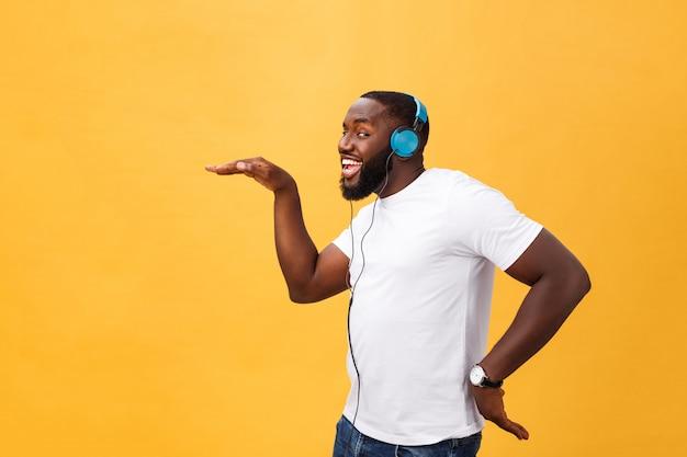 ヘッドフォンを身に着けている若いアフリカ系アメリカ人男性と黄色の金の背景の上で踊る音楽を楽しむ