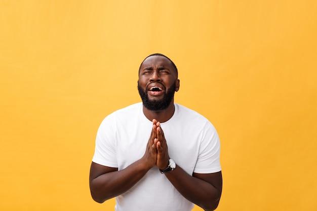 祈りで手を繋いでいる白いシャツの若いアフリカ系アメリカ人のスタジオポートレート
