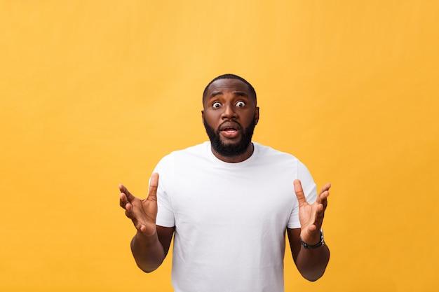 ショックと不信で育った手でアフリカ系アメリカ人の男の肖像画。黄色の背景に分離しました。
