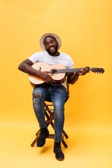 彼のギターを弾く興奮して芸術的な男の全身像。黄色の背景に分離されました。