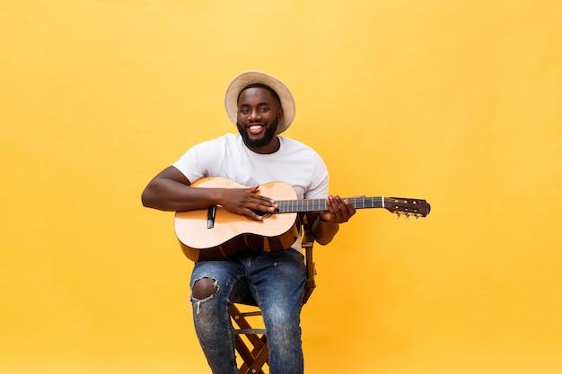 ハンサムなアフリカ系アメリカ人のレトロな黄色の背景に分離されたアコースティックギターを弾くギタリスト。