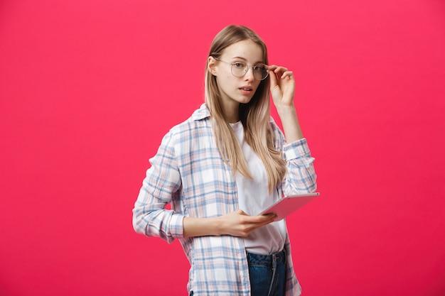 タブレットを保持している若いビジネス女性とピンクの背景について考えています