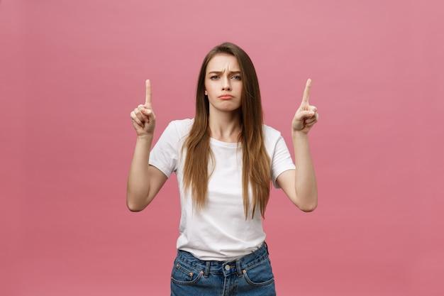 Макрофотография серьезной строгой молодой женщины носит белую рубашку выглядит подчеркнул и направлен вверх