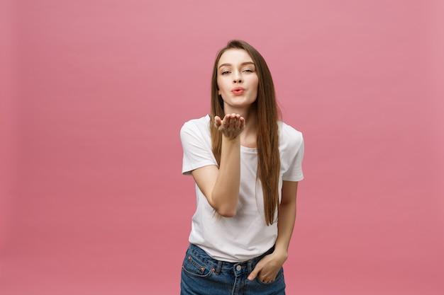 Красивая женщина с макияжем и длинными светлыми волосами дует поцелуй