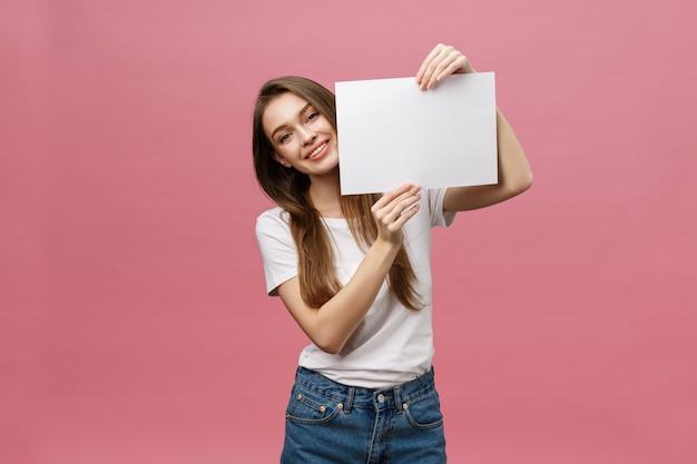 笑みを浮かべて、白い大きなモックアップポスターを保持している肯定的な笑い女の肖像画を間近します。
