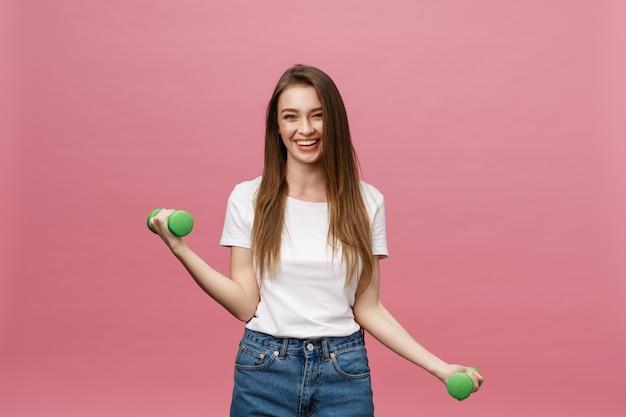 フィットネス、スタジオの背景でダンベルを持つ若い女。