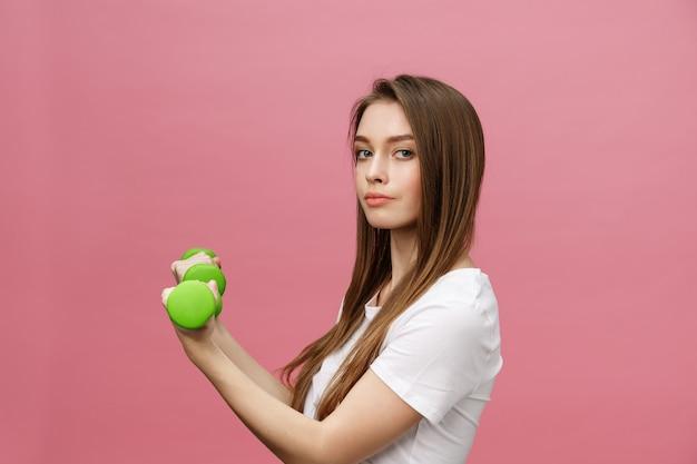 フィットネス、スタジオの背景でダンベルを持つ若い女。かわいい女の子をピンクの上分離