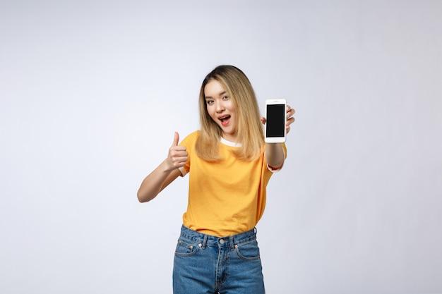 黄色のシャツを着た若いアジア女性が白い背景の上のサインを親指を見せています。