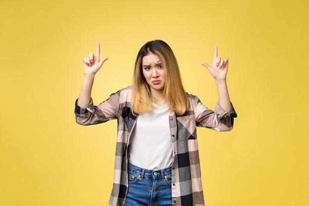 不幸な感情で指を指す若い魅力的なアジアの女性。