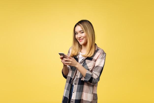 長い髪の笑顔と携帯電話でテキストメッセージで満足しているアジアの女性のイメージ
