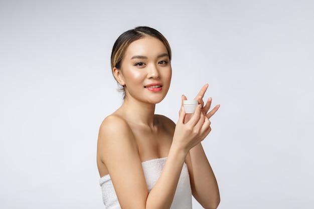 美しいアジアの女性が白い背景で隔離の製品を提示します。