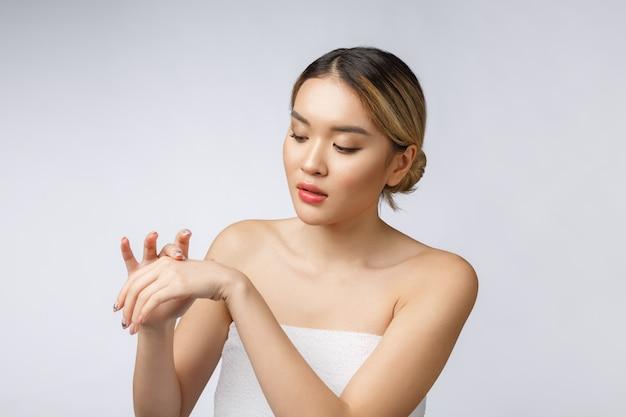 アジアの女性の分離の白い背景の上の肌に化粧品クリームを適用します。