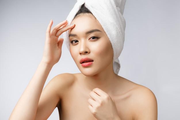アジアの女性が顔ににきびを見ています。若い女性は彼女のにきびを削除しようとすると