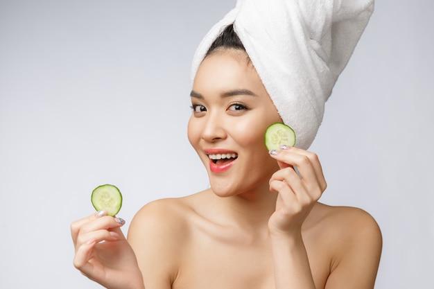 白い背景のスタジオでキュウリの美しさ若いアジア女性スキンケア画像。