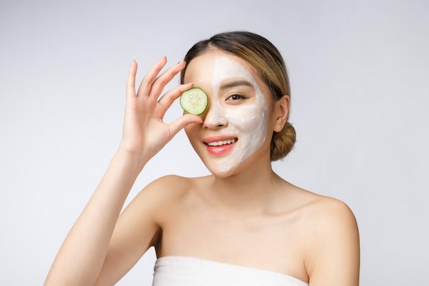 きゅうりを保持している完璧な肌を持つアジアの若い美しい笑顔の女性