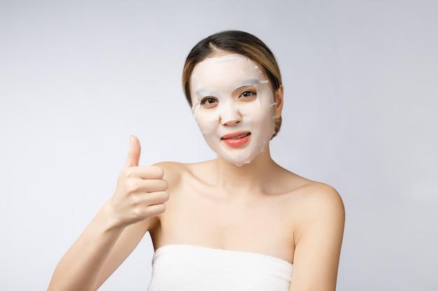 スパ、ヘルスケア親指を現して化粧品マスクを持つアジアの女の子。