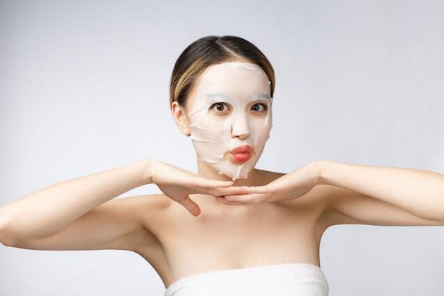 スパ、ヘルスケア化粧品マスクを持つアジアの女の子は白で隔離します。