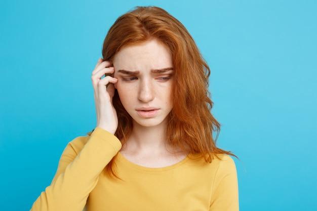 注目のカメラを見て真剣な表情で優しい赤毛の十代の少女の顔の肖像画。屋内でポーズを取るジンジャーヘアの白人女性モデル。パステルの青い背景。スペースをコピーします。