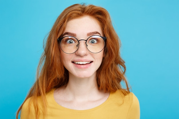 クローズアップ肖像画若い美しい魅力的な赤毛の女の子は何かとショックを眼鏡で。青いパステルの背景。スペースをコピーします。