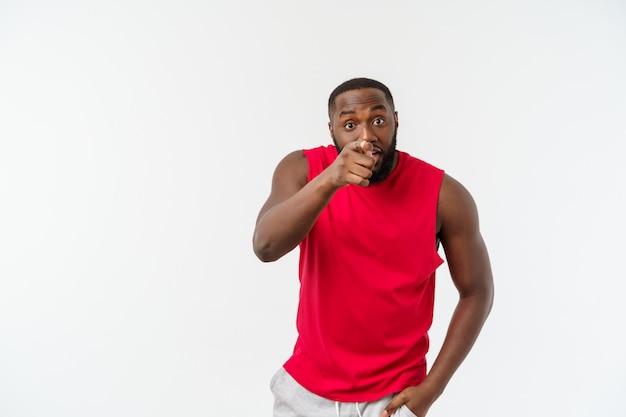 Молодой афроамериканец спортивный человек, указывая пальцем с удивлен, чувствует себя успешным и процветающим