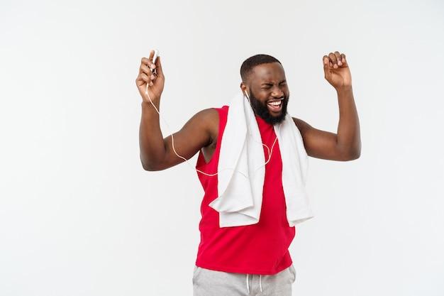Музыка красивого человека афроамериканца слушая на его мобильном устройстве после тренировки спорта.