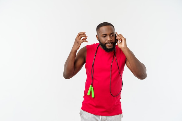 成熟した携帯電話で話していると、弾性ロープを保持しているアフリカ系アメリカ人の男に合います。