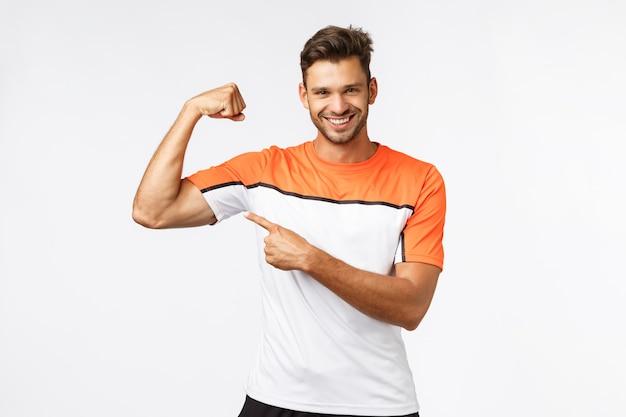 Парень хвастается мускулами, спрашивая, хочешь ли ты прикоснуться или обрести такую хорошую форму тела.