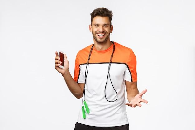 Красивый, сексуальный спортсмен использует приложение для фитнеса на смартфоне, чтобы отслеживать свой результат