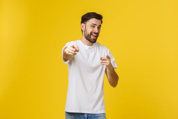 黄色の壁に分離されたコピースペースを示すポインティング男。カジュアルなハンサムな白人の若い男。