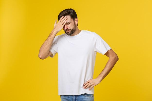 重度の頭痛に苦しんでいる、黄色い壁に分離された若い男の肖像