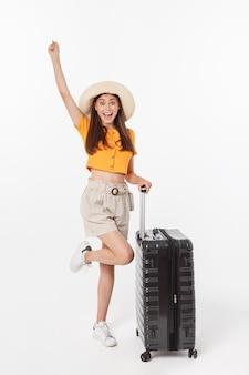 Женщина турист. полнометражная счастливая молодая женщина стоя с чемоданом с захватывающим показывать, изолированный на белой стене.