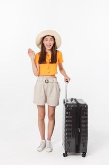 女性観光客。エキサイティングなジェスチャーでスーツケースに立って、白い壁に分離された完全な長さの幸せな若い女性。