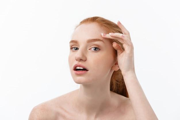赤毛の女性は彼女の顔ににきびの指を示しています。