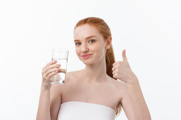健康、人々、食べ物、スポーツ、ライフスタイル、美容コンテンツ-水のガラスを持つ若い女性の笑みを浮かべてください。