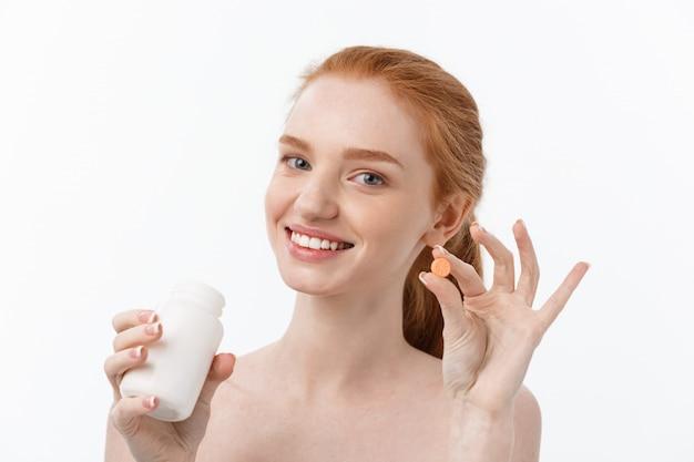 Красивая девушка улыбается, принимая лекарства, держа бутылку с таблетками. здоровая счастливая женщина ест таблетки. витамины и пищевые добавки, концепция диетического питания