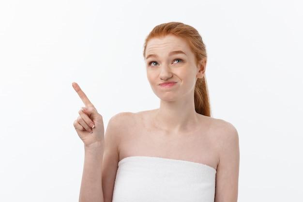 白い背景の上の人差し指を脇に指して、心配とショックでかわいい白人の肖像画。
