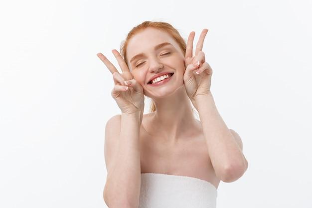 Крупным планом красивой молодой женщины с банное полотенце, охватывающих ее груди, на серый, показывает два пальца знак.