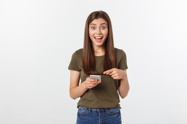 Смеясь над женщина говоря и отправляя смс на телефоне изолированном на белизне.