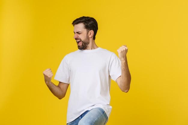黄色で分離された腕を持つ幸せな若い男。