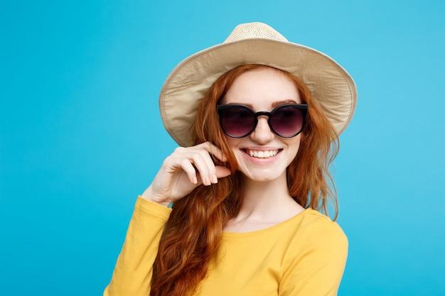 旅行のコンセプト - クローズアップ肖像画若い美しい魅力的なジンジャー赤い髪の女の子と笑顔のトレンディな帽子とサングラス。青いパステルの背景。スペースをコピーします。