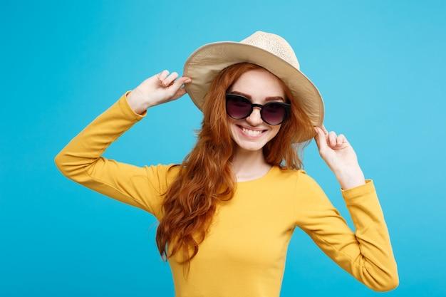 旅行のコンセプト - クローズアップ肖像画若い美しい魅力的な赤毛の女の子と笑顔のトレンディな帽子とサングラス。青いパステルの背景。スペースをコピーします。