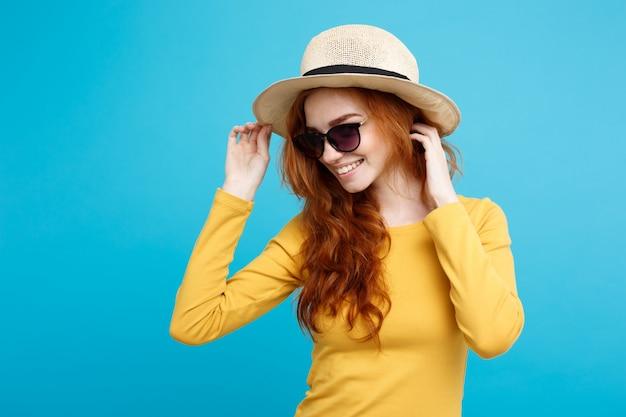 旅行の概念 - クローズアップ肖像画若い美しい魅力的な赤毛の女の子と流行の帽子とサングラス笑顔。青いパステルの背景。スペースをコピーします。