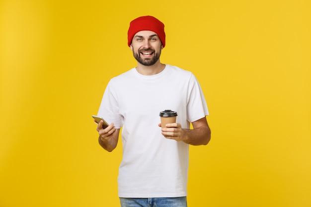 Портрет жизнерадостного молодого человека нося вскользь одежды стоя изолированный над желтым цветом, держащ мобильный телефон, выпивая на вынос кофе.