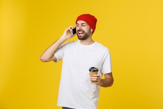黄色の上分離された立っているカジュアルな服を着て、携帯電話を保持しているテイクアウトコーヒーを飲んで陽気な若い男の肖像画。