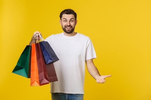 黄色で分離された買い物袋を保持している幸せな男の写真