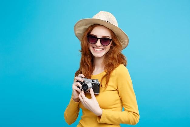 旅行のコンセプト - クローズアップ流行の帽子、サングラス、カメラに笑顔のヴィンテージカメラと肖像画の若い美しい魅力的な赤毛の女の子。青いパステルの背景。スペースをコピーします。