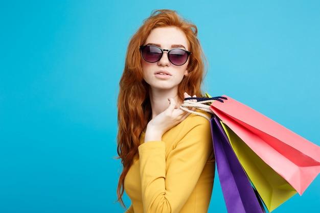 ショッピングコンセプト - クローズアップ肖像画の若い美しい魅力的な赤毛の女の子ショッピングバッグでカメラを見て笑っている。青いパステルの背景。スペースをコピーします。