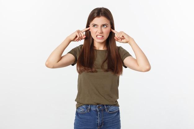 彼女の耳を覆っている怒っている若い女性のクローズアップの肖像画は、白で隔離され、頭痛を与えている大きな音を立てることを停止します。